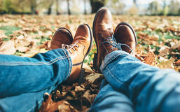 Clouse up image couple in love legs in comfortable laser shoes a. Close up image couple in love legs in comfortable leather shoes and denim pants Stock Photography