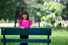 Clouse-up portrait pretty little girl sitting on a bench Royalty Free Stock Photos