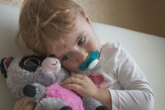 Clouse-up portrait small child sitting on the bed in the room hugging a stuffed toy lemur. horizontal royalty free stock photo