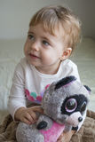 Clouse-up portrait small child sitting on the bed in the room hugging a stuffed toy lemur stock image