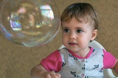 Clouse-up portrait two-year girl inflates a large circular bubble stock photography