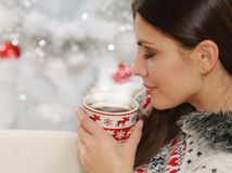 Clouse up shot of an attractive young woman enjoying hot drink o Stock Photos