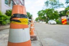 Clouse-up un cono di traffico sulla strada con il fondo della sfuocatura Immagini Stock Libere da Diritti