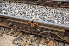 Clouse up vew of metal railway track. Detail of railway track construction on gravel for train transportation system royalty free stock image