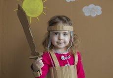 Clouse-upporträt des netten kleinen Mädchens mit einer Pappklinge und einer Klage handmade Hintergrund der gemalten Sonne und Stockbilder