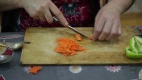 Clouseup van een vrouw in de keuken bereidt kruidige wortelsalade voor stock videobeelden