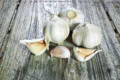 Clove of garlic and peeled on old wood background Stock Images