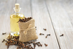 Clove oil. On the glass bottle and bag with cloves Stock Photo