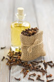 Clove oil. On the glass bottle and bag with cloves Royalty Free Stock Images