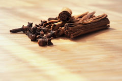 Clove spice cinnamon sticks on a wooden board Royalty Free Stock Images