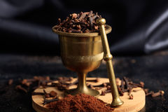 Clove spice seeds and powder. On a black background Royalty Free Stock Photography