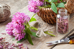 Clover, bottle with dried herb and basket with flowers Royalty Free Stock Photo
