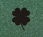 Clover with four leaves, Black on a glittery green background. Royalty Free Stock Photos