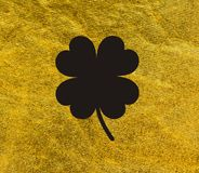 Clover with four leaves Black on golden background Stock Photos