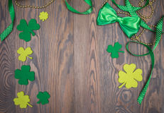 Clover leaves, gold beads, ribbons and bow tie green traditional Irish decoration Royalty Free Stock Image