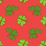 Clover seamless pattern. Clover pattern with three and four leaf. Green on red background. St. Patrick`s Day hand-drawn doodle style clover endless repeat Stock Images