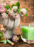 Clover in a stone mortar with a candle Royalty Free Stock Images