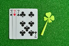 A clover and three number seven cards. On a green background Royalty Free Stock Image