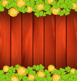 Clovers and golden coins on brown wooden background Stock Photo