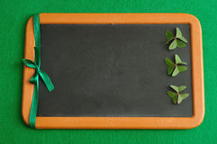 Clovers and a green ribbon displayed on a black board. For St, Patrick's day Royalty Free Stock Photography