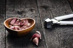 Cloves czosnek na drewnianym czerń stole Świeża czosnek żarówka z żelazną czosnek prasą ornamentu geometryczne tła księgi stary r Zdjęcia Stock