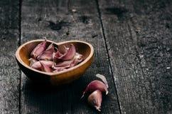 Cloves czosnek na drewnianym czerń stole Świeża czosnek żarówka z żelazną czosnek prasą ornamentu geometryczne tła księgi stary r Fotografia Stock
