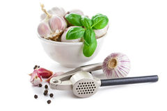 Cloves of garlic, basil and garlic press Royalty Free Stock Image