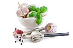 Cloves of garlic, basil and garlic press royalty free stock image