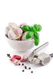 Cloves of garlic, basil and garlic press Royalty Free Stock Photos
