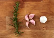 Cloves of garlic and  fresh organic rosemary on wooden chopping board Royalty Free Stock Image