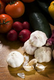 Cloves of garlic with other vegetables. Cloves of fresh garlich with many more vegetables on wooden table Stock Image