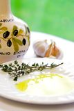 Cloves of garlic and sprig of fresh thyme. Soaked in virgin olive oil, ready for culinary preparation Royalty Free Stock Images