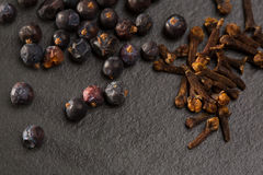 Cloves and juniper berries spices on black slate stone Stock Photography