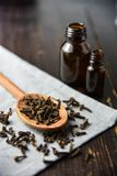 Cloves, old wooden background, selective focus oil bottle. Bottles Royalty Free Stock Image