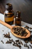 Cloves, old wooden background, selective focus oil bottle. Bottles Stock Images