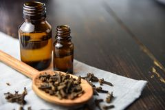 Cloves, old wooden background, selective focus oil bottle. Bottles Stock Photo