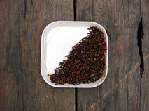 Cloves in the plate on wooden board. Lots of cloves in the plate on wooden board royalty free stock images