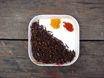 Cloves, red chilli, turmeric setting in the plate. Lots of cloves with red chilli and turmeric in the plate on wooden board royalty free stock photo