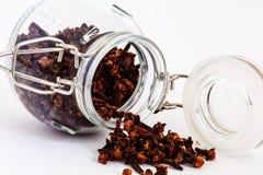 Cloves spilling from glass jar Stock Photos