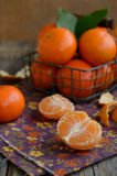 Cloves of tangerines and wire basket full of ripe fruits Royalty Free Stock Photos
