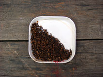 Cloves in the white plate. On wooden board Royalty Free Stock Images
