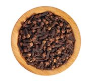Dried cloves in a wooden bowl on a white background. Cloves in wooden bowl isolated on white. Whole cloves.Top view Royalty Free Stock Image