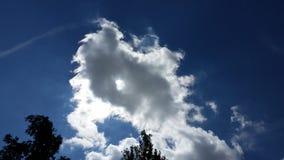 Clowds med solsolen som igenom kikar Arkivfoto