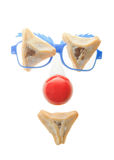 Clown's face - Purim arrangement with Hamentashen. Clown's face - Purim arrangement with Hamentashen,Funny glasses and a red nose Royalty Free Stock Image