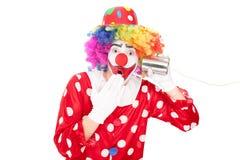 Clown étonné écoutant par un téléphone de boîte en fer blanc Images libres de droits