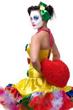 Clown. Adult female clown holding red heart behind his back Stock Photos