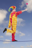 Clown as a tightrope walker with flower Royalty Free Stock Image