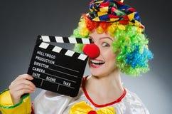 Clown avec le clapet de film dans le concept drôle Images libres de droits