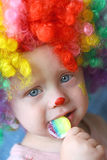 Clown Baby with Sucker. Close up of a cute baby boy dressed up in a clown costume, eating a rainbow sucker Stock Images