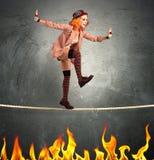 Clown balance on fire. Clown balancing on a rope over fire stock photos